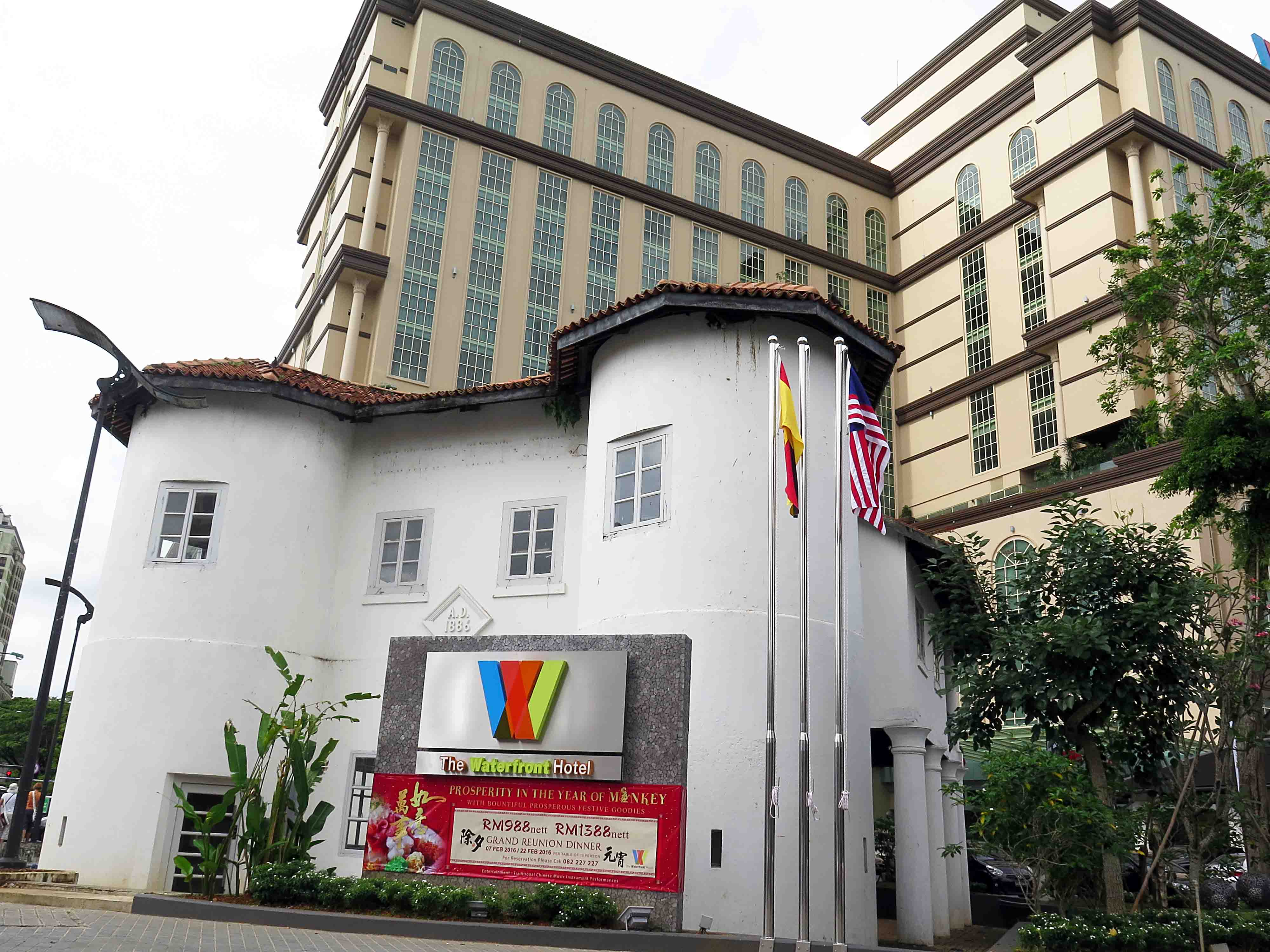 Round Tower, Kuching, still partly obscured by signboard(s), and now also flagpoles, for the hotel located at its back (30 Jan. 2016 photo)